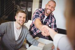 Hombres de negocios que sacuden las manos en oficina creativa Fotografía de archivo