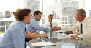 Hombres de negocios que sacuden las manos en una reunión almacen de video