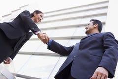 Hombres de negocios que sacuden las manos fuera de la oficina Foto de archivo