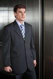 Hombres de negocios que salen del elevador Imágenes de archivo libres de regalías