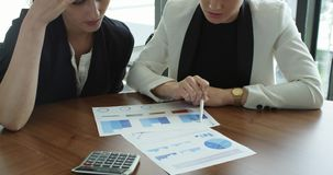 Hombres de negocios que señalan en los diagramas