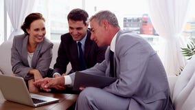 Hombres de negocios que señalan en un ordenador portátil almacen de video