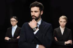 Hombres de negocios que se colocan con los brazos cruzados aislados en el negro, concepto del establecimiento de negocio Imagenes de archivo