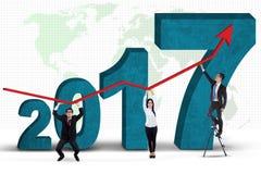 Hombres de negocios que se colocan con los números 2017 y el gráfico Fotografía de archivo libre de regalías