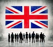 Hombres de negocios que se colocan delante de la bandera BRITÁNICA Fotos de archivo libres de regalías