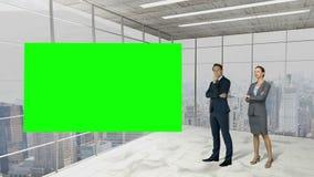 Hombres de negocios que se colocan delante de una pantalla almacen de video