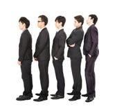 Hombres de negocios que se colocan en una línea imagenes de archivo