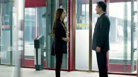 Hombres de negocios que se encuentran y que hablan en área del elevador metrajes