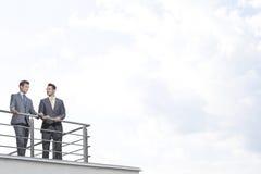 Hombres de negocios que se oponen en las verjas de la terraza al cielo nublado Imagen de archivo