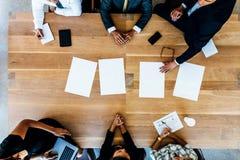 Hombres de negocios que se sientan alrededor de una tabla con las hojas en blanco fotos de archivo