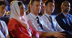 Hombres de negocios que se sientan en asientos en el auditorio 4k almacen de metraje de vídeo