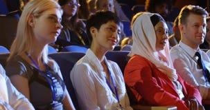 Hombres de negocios que se sientan en asientos en el auditorio 4k metrajes