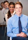 Hombres de negocios que se sientan en fila Fotografía de archivo