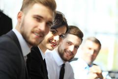 Hombres de negocios que se sientan en fila y que trabajan, foco en mujer joven Fotos de archivo