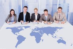 Hombres de negocios que se sientan en la mesa de reuniones con el mapa del mundo Fotos de archivo