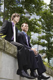Hombres de negocios que se sientan en la pared fuera de la oficina imagen de archivo libre de regalías