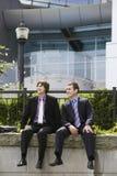 Hombres de negocios que se sientan en la pared fuera de la oficina imagenes de archivo