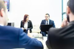 Hombres de negocios que se sientan en la reunión de funcionamiento en oficina corporativa moderna Imagen de archivo