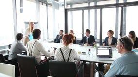 Hombres de negocios que se sientan en la tabla mientras que colega femenino que da la presentación almacen de video