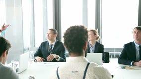 Hombres de negocios que se sientan en la tabla mientras que colega femenino que da la presentación almacen de metraje de vídeo