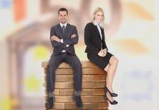 Hombres de negocios que se sientan en monedas apiladas Fotografía de archivo