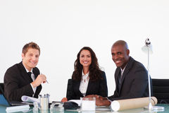 Hombres de negocios que sonríen a la cámara en una reunión Foto de archivo libre de regalías