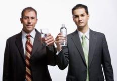 Hombres de negocios que sostienen el agua Imagen de archivo libre de regalías