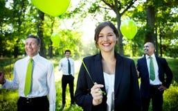 Hombres de negocios que sostienen el globo verde en bosque imagen de archivo