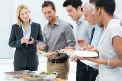 Hombres de negocios que tienen comida junto