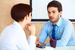 Hombres de negocios que tienen conversación con el colega durante rotura imágenes de archivo libres de regalías