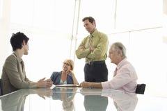 Hombres de negocios que tienen discusión en la mesa de reuniones Imágenes de archivo libres de regalías
