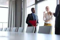 Hombres de negocios que tienen discusión mientras que hace una pausa la mesa de reuniones en oficina Imágenes de archivo libres de regalías