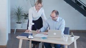 Hombres de negocios que tienen reunión alrededor del vector en oficina moderna almacen de metraje de vídeo
