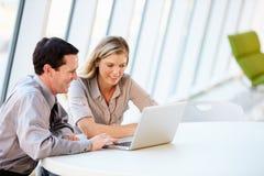 Hombres de negocios que tienen reunión alrededor del vector en oficina moderna Imagen de archivo libre de regalías