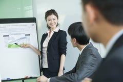 Hombres de negocios que tienen reunión, haciendo una presentación Imagen de archivo libre de regalías