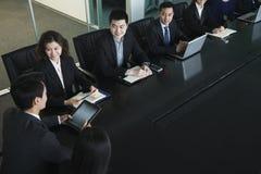 Hombres de negocios que tienen reunión, sentada en la mesa de reuniones Fotografía de archivo libre de regalías