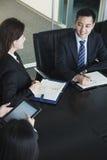 Hombres de negocios que tienen reunión, sentada en la mesa de reuniones Fotos de archivo