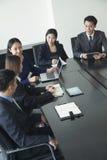 Hombres de negocios que tienen reunión, sentada en la mesa de reuniones Imagen de archivo