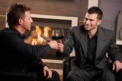 Hombres de negocios que tintinean los vidrios de vino Imágenes de archivo libres de regalías