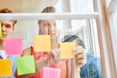 Hombres de negocios que toman notas en notas pegajosas Fotografía de archivo libre de regalías