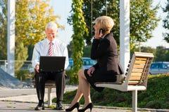 Hombres de negocios que trabajan al aire libre Foto de archivo