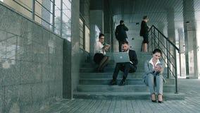 Hombres de negocios que trabajan al aire libre sentarse en las escaleras en un día de verano metrajes