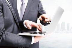 Hombres de negocios que trabajan con el ordenador portátil en el fondo de la ciudad Imagen de archivo libre de regalías