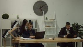 Hombres de negocios que trabajan con el ordenador portátil en el lugar de trabajo metrajes