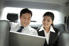 Hombres de negocios que trabajan con el ordenador portátil en el coche Imagen de archivo libre de regalías
