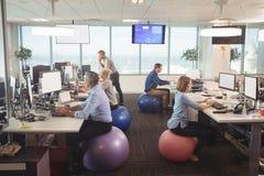 Hombres de negocios que trabajan en el escritorio mientras que se sienta en bolas del ejercicio imágenes de archivo libres de regalías
