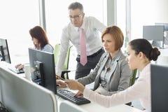Hombres de negocios que trabajan en el ordenador en oficina Fotografía de archivo