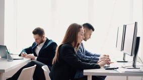 Hombres de negocios que trabajan en el ordenador en su lugar de trabajo almacen de video