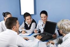 Hombres de negocios que trabajan en la computadora portátil en la reunión Imágenes de archivo libres de regalías