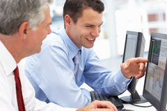 Hombres de negocios que trabajan en los ordenadores Foto de archivo libre de regalías